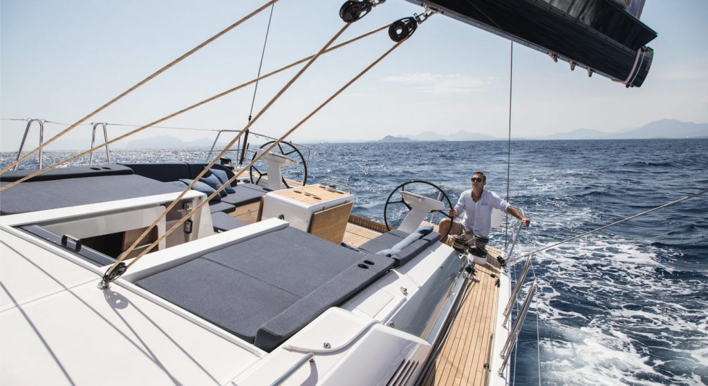 Man driving a oceanis 51.1 sailing yacht.